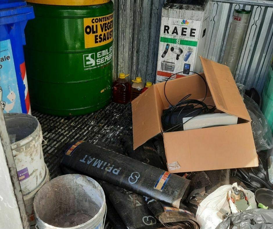 Bidone olii esausti circondato da rifiuti